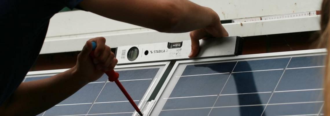 Wasserwaage an eine Solarpanele halten