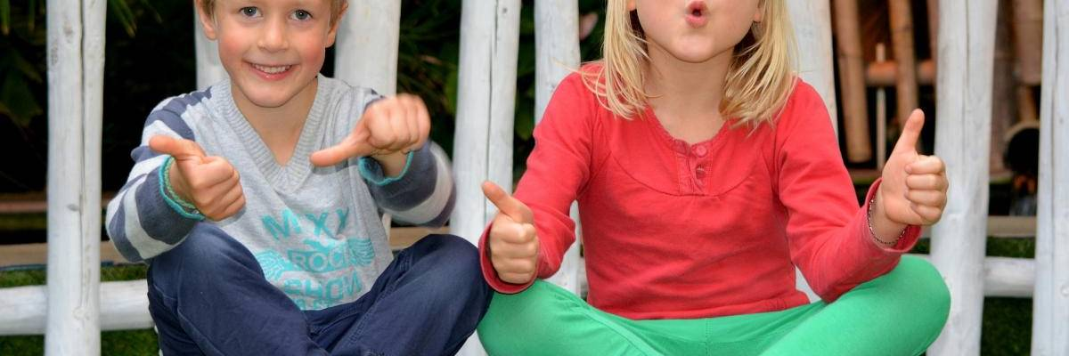 Zwei Kinder sitzen auf einem Stein und zeigen Daumen hoch und Daumen seitwärts ©Pixabay