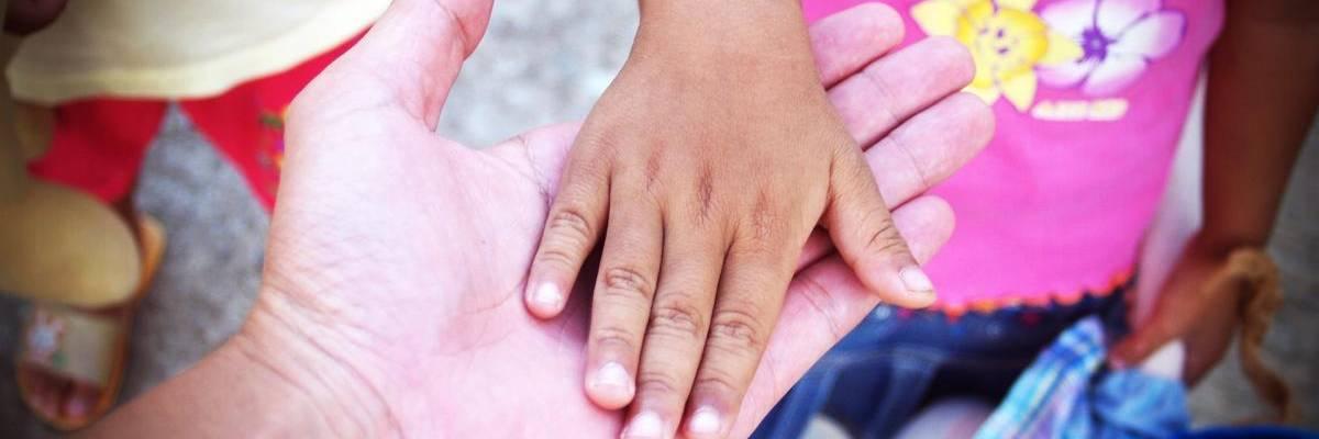 Kinderhand liegt in einer geöffneten Erwachsenenhand ©Pixabay