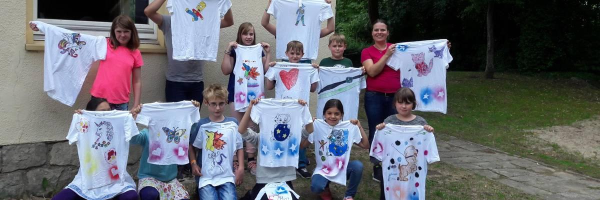 Gruppe von Kinder mit Betreuerin halten selbst bemalte T-Shirts hoch ©Stadt Laatzen © Stadt Laatzen