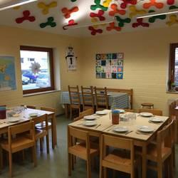 Timmer mit mehreren gedeckten Tischen und Bildern an der Wand