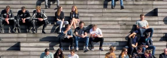 Mehrere Jugendliche sitzen auf einer breiten Treppe verteilt auf den Stufen