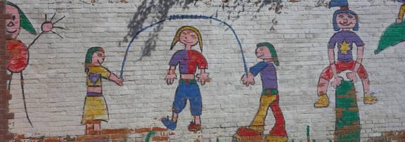 Eine Mauer ist mit Seil springenden Kinder bemalt