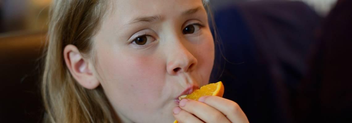 Mädchen ist eine Orangenscheibe