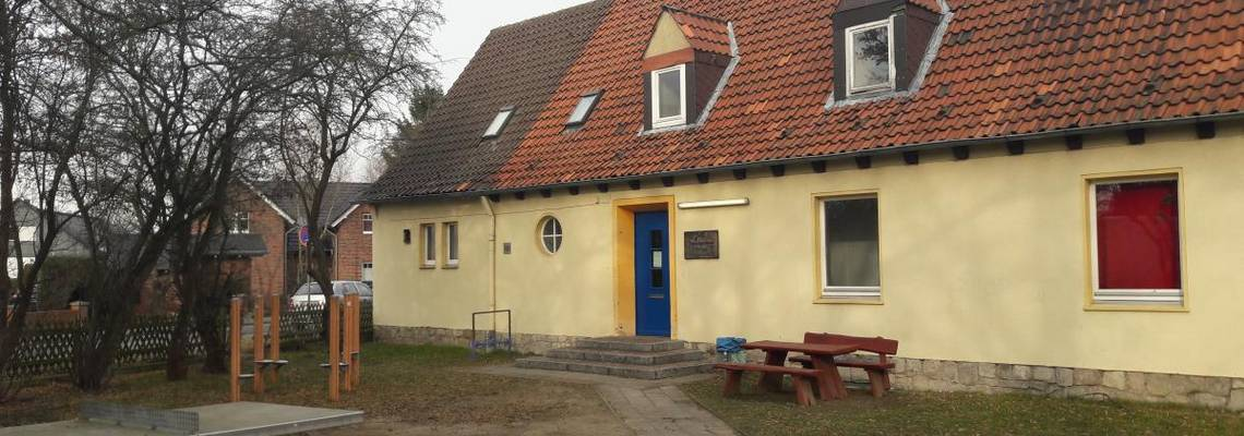 Blick auf die Vorderseite. Gelbes Haus mit rotem Dach und blauer Eingangstür