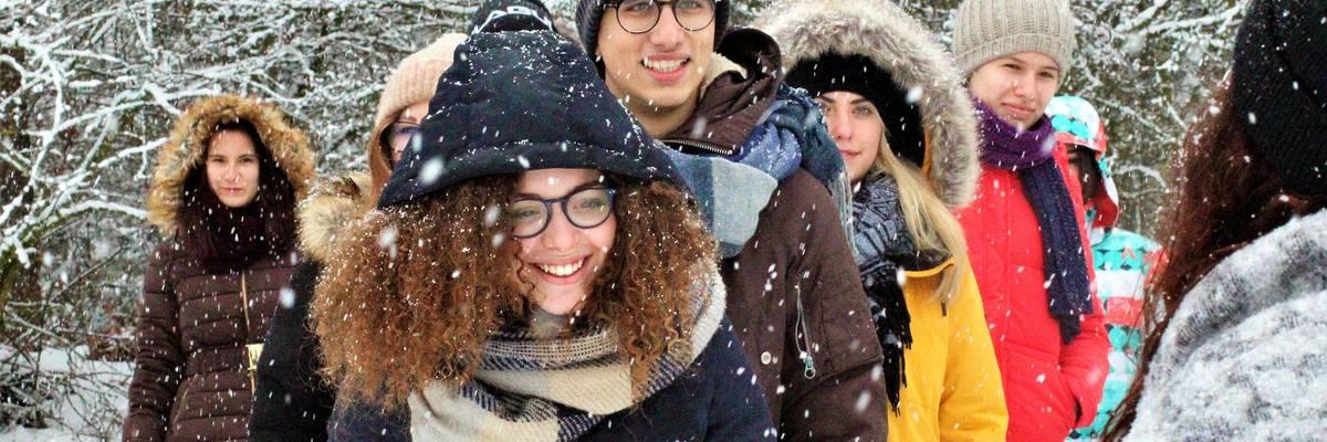 Gruppe von Jugendlichen steht vor Schneebedeckten Bäumen. Es schneit. ©Pixabay