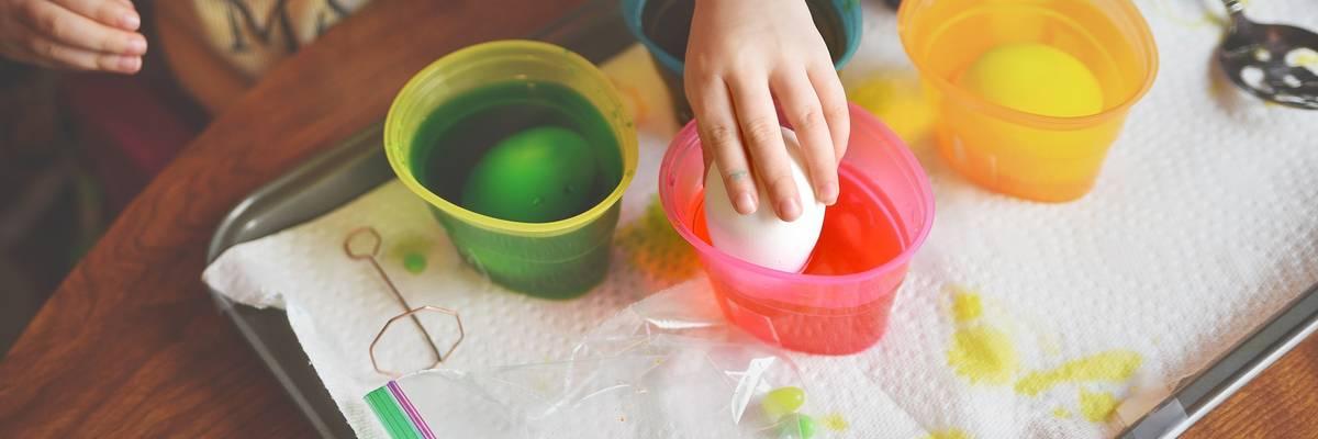 Fünf Farbbecher. Kinderhand hält ein Ei über eine Becher ©Pixabay