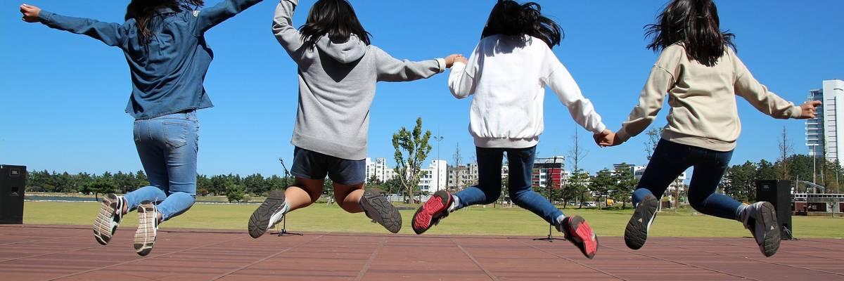Jugendliche halten sich an der Hand und springen