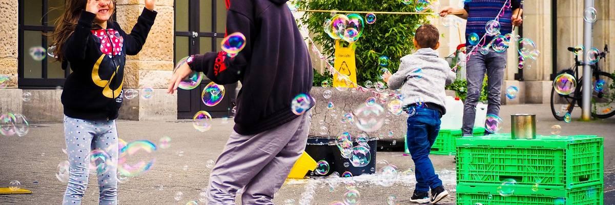 Mehrere Kinder und Jugendliche stehen in einer Wolke aus Seifenblasen ©Esther Schwab