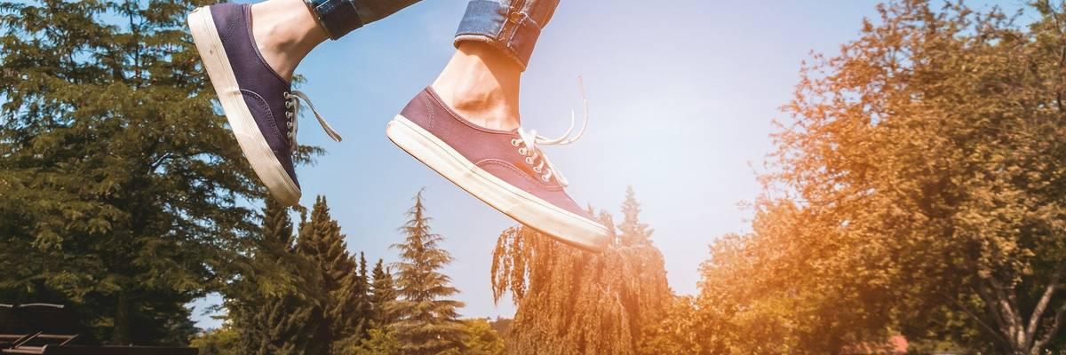 Lichtung mit Blumenwiese und Sonne im Hintergrund. Davor Füße eines springenden Jugendlichen ©Pixabay
