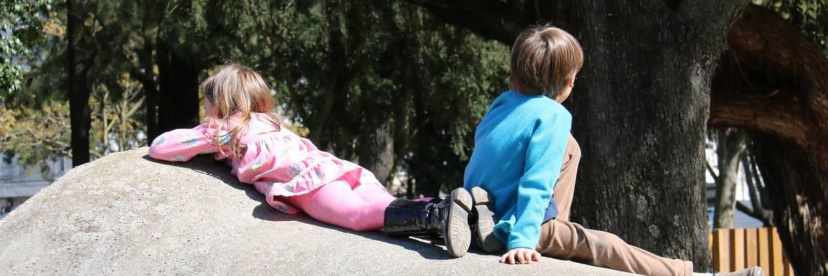 Ein Junge und ein Mädchen sitzen bzw. liegen auf einer Betonröhre ©Pixabay