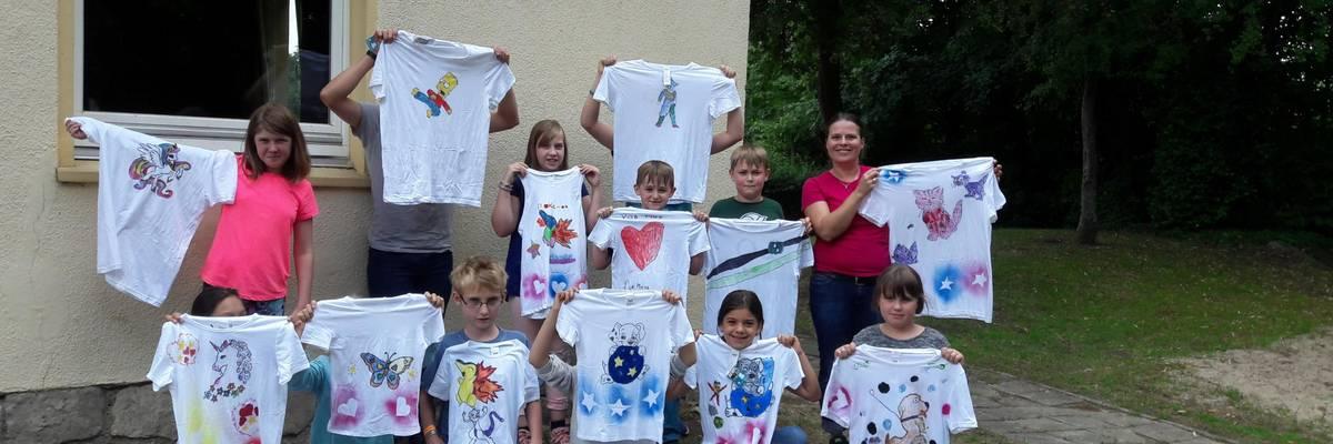 Gruppe von Kinder mit Betreuerin halten selbst bemalte T-Shirts hoch ©Stadt Laatzen