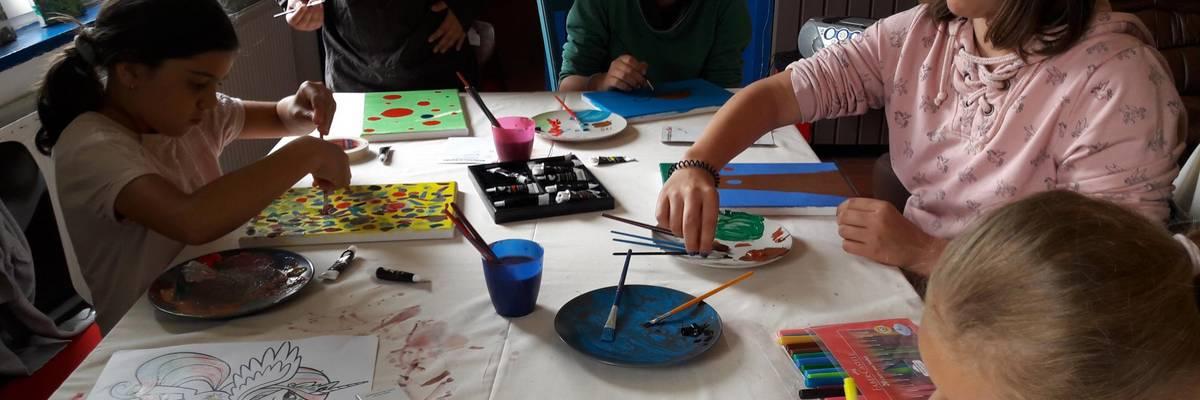 Kinder sitzen an einem Tisch und bemalen Leinwände ©Stadt Laatzen