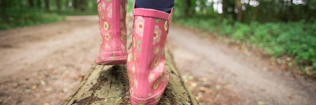 Zwei Füße mit Gummistiefeln balancieren auf einem Baumstamm