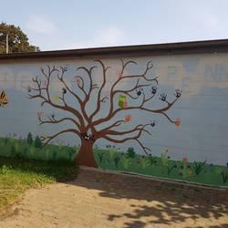 Hauswand, die mit einem Baum, Gras, hellblauem Himmel, Blumen und Tieren bemalt ist