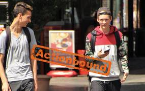 Zwei Jungen laufen nebeneinander und haben ihre Handys in der Hand
