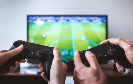 Es sind die Hände zweier Spieler zu sehen, die jeweils einen Controller halten und im Hintergrund befindet sich ein Fernseher mit FIFA ©Pixabay