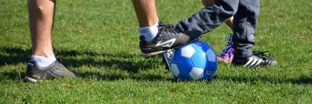 Fuß, der auf einem blauen Fußball steht