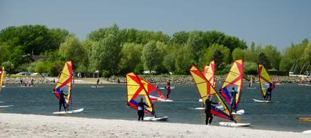 Strand, Meer, mehrere Personen auf Surfbrettern