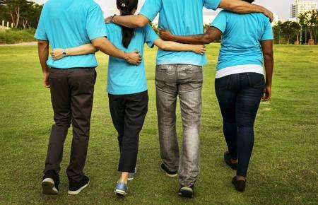 Vier junge Menschen gehen Arm in Arm