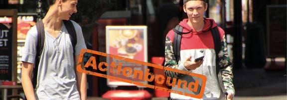 Zwei Jungen mit Handy sind in einer Stadt unterwegs, Stempel Actionbound auf dem Bild