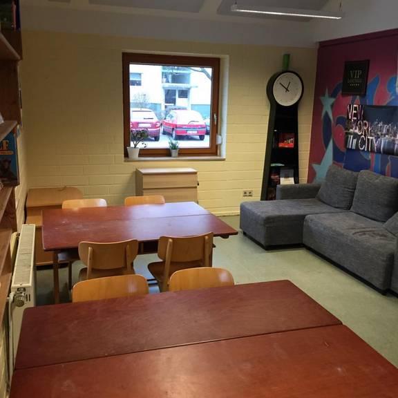 Zimmer mit Tischen, Stühlen und einem Sofa
